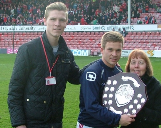 Jay Harris, the first winner of the trophy, receives it from Steve's widow Wendy and his commentary colleague Alex Taylor.